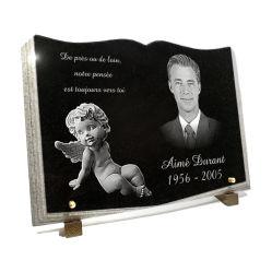 Plaque granit taill� en livre ouvert, portrait photo, ange et texte fun�raire grav�s.