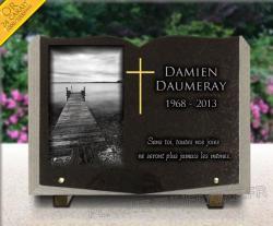 Plaque funéraire en granit forme livre ouvert. Dessin gravé mer et croix chrétienne dorée