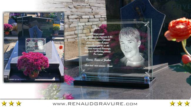 Engraved glass memorial plaque on granite base.