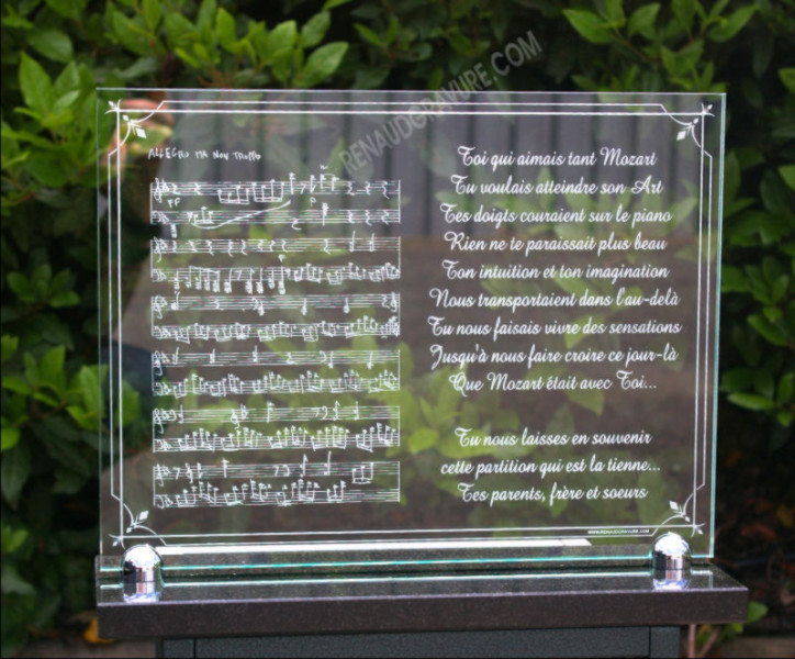 A glass funeral plaque with musical notes and music score